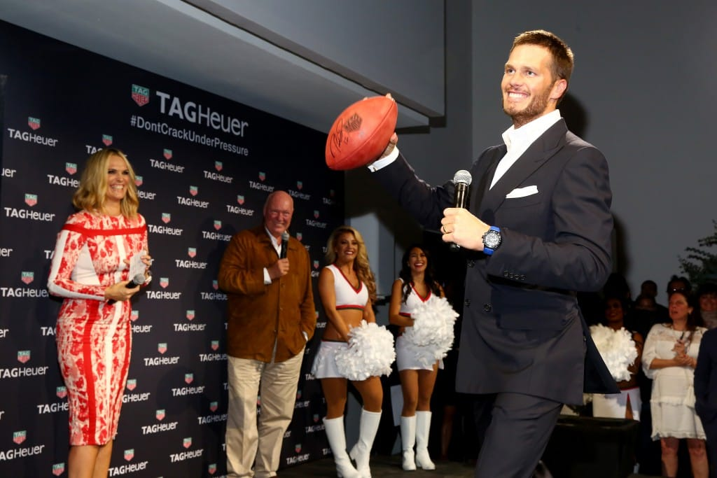 Tom Brady throwing signed footballs to raise money for the Best Buddies charity.